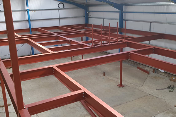 An image showing some metal I beams we fabricated now being used to create a building
